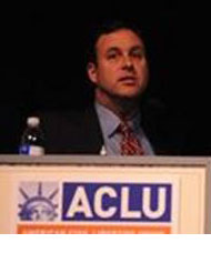 Man standing at a podium with an ACLU logo on it