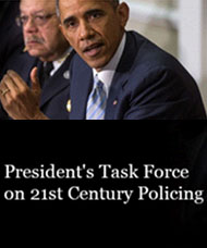 "A poster showing a picture of Barack Obama and another man above the words ""President's Task Force on 21st Century Policing"""