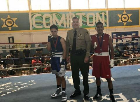 Capt. Michael Thatcher poses for a photo with two boxers competing in a match with the Compton Sheriff Youth Activities League.